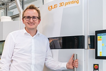 Tom Krause stands in front of an SLS 3D printer